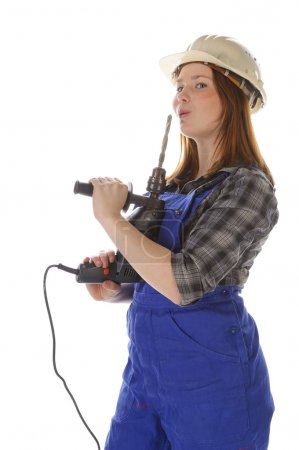 Photo pour Jeune femme (Erin Crafts, bricoleuse, stagiaire) aux longs cheveux blonds portant une chemise à carreaux et une salopette de travail bleue. Elle tient une perceuse électrique. - image libre de droit