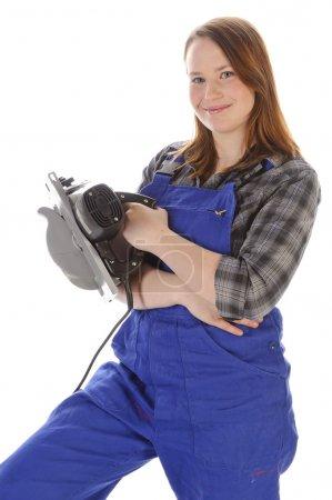 Photo pour Jeune femme (Erin Crafts, bricoleuse, stagiaire) aux longs cheveux blonds portant une chemise à carreaux et une salopette de travail bleue. Elle tient une scie dans sa main. . - image libre de droit