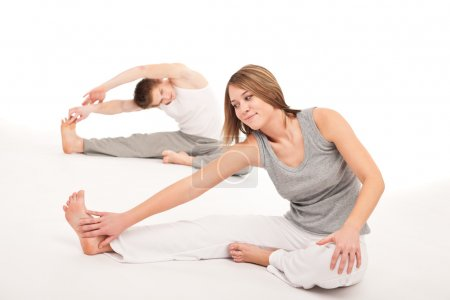 Fitness - Healthy couple stretching after training on white