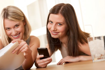 Foto de Dos estudiantes sonrientes disfrutando de tiempo libre con el libro y el teléfono móvil - Imagen libre de derechos