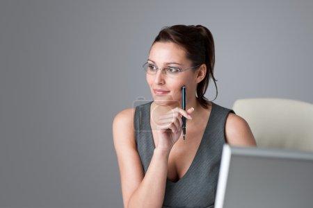 Photo pour Réussir femme d'affaires exécutif penser au bureau, tenant stylo - image libre de droit