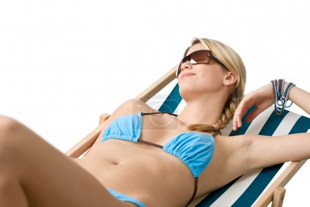 Beach - Young woman in bikini lying on deck chair