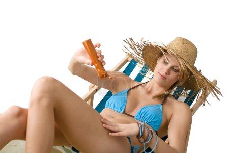 Beach - Young woman apply suntan lotion