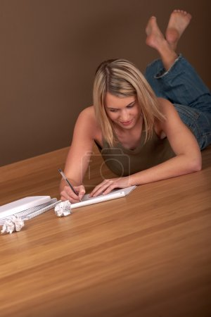 Student series - Blond young woman writing homework