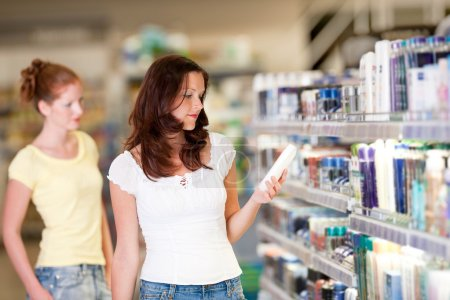Photo for Woman holding bottle of shampoo in cosmetics department - Royalty Free Image