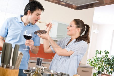Happy couple cook in kitchen tasting food