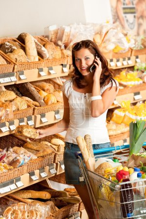Grocery store: Young woman with mobile phone