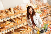 Grocery store: Young woman buying bread
