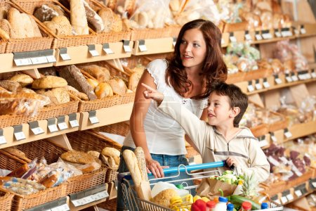 Photo for Grocery store shopping - Woman with child in a supermarket choosing bread - Royalty Free Image