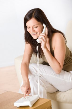 On the phone home: smiling woman dialing number calling