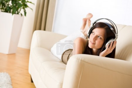 Photo for Woman with headphones listen to music in lounge, plant in background - Royalty Free Image