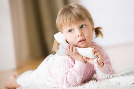 Little girl lying down on carpet with phone calling