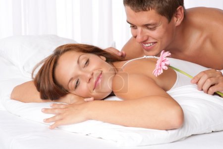 Happy man and woman lying down in bed together