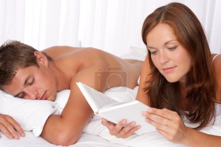 Young couple lying down in bed