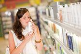 Shopping cosmetics - woman smelling shampoo