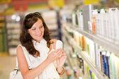 Shopping cosmetics- smiling woman holding shampoo