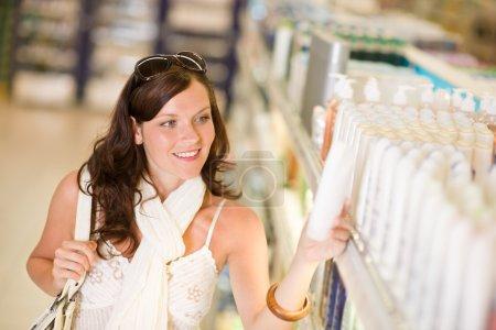 Shopping cosmetics - smiling woman choose shampoo