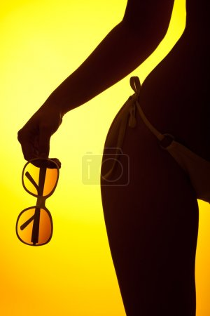 Photo for Silhouette of female body with bikini and sunglasses on yellow background, back lit - Royalty Free Image