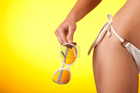 Photo for Part of female body with white bikini and sunglasses on yellow background - Royalty Free Image