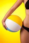 Part of female body wearing black bikini and holding beach ball
