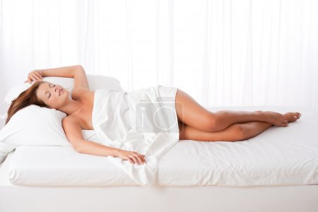 White lounge - Long shot of woman lying in bed