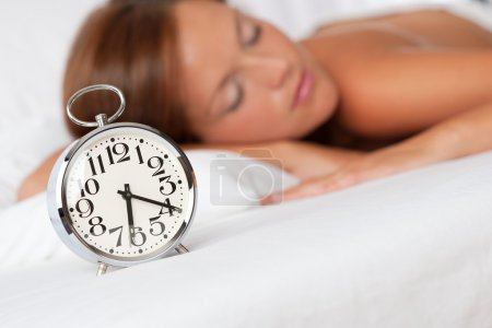 White lounge - Silver alarm clock on white bed