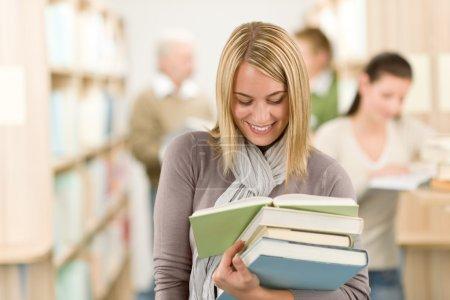 Photo pour Bibliothèque de l'école secondaire - étudiante heureux avec le livre lu - image libre de droit
