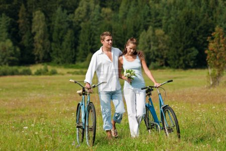 Romantic young couple walking with old bike