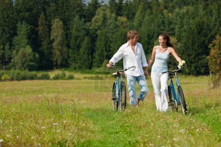 Photo for Romantic young couple with old bike in spring nature on sunny day - Royalty Free Image