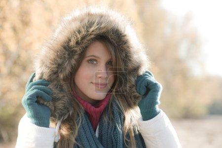 Foto de Moda invierno - mujer con capucha de piel y guantes afuera, desaturar colores - Imagen libre de derechos