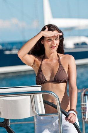 Beautiful young woman standing on luxury boat