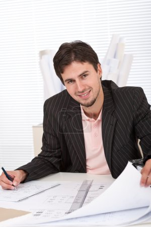 Successful architect man working with plans
