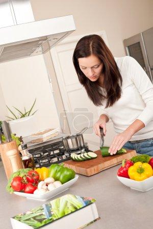 Happy woman cutting zucchini in the kitchen