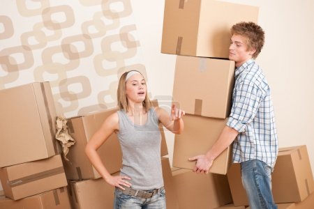 Photo for Moving house: Man and woman with box in new home - Royalty Free Image