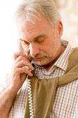 Zamyšleně starší zralý muž volání na telefon