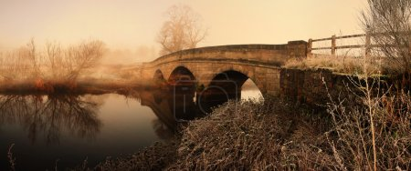 Photo for Bridge in morning mist fog or haze. panoramic image of old stone construction - Royalty Free Image