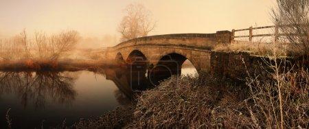 Photo pour Pont dans la brume matinale brouillard ou brume. image panoramique de la vieille construction en pierre - image libre de droit