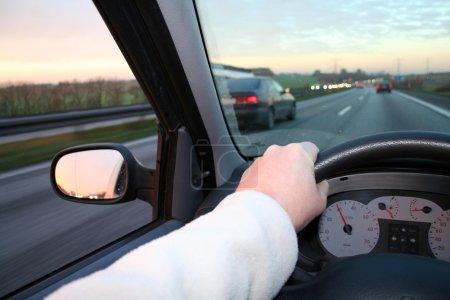 Photo pour Volant de direction de voiture. main tenant la roue tout en dépassement de la voiture. promenade au crépuscule avec coucher de soleil à l'horizon - image libre de droit