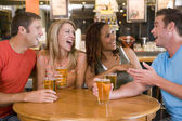 Skupina mladých přátel, pití a směje se v baru