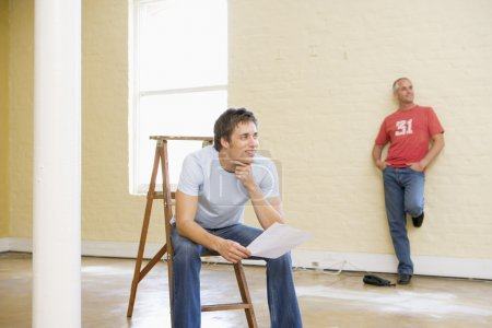 Two men with ladder in empty space one holding paper smiling