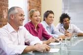 čtyři podnikatelé v zasedací místnosti s úsměvem