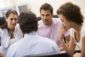 Muž dává přednášku na tři v počítačové místnosti