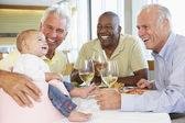 Muž ukazující jeho vnučka dítě s přáteli v restauraci