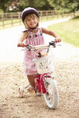 Girl Learning To Ride Bike Wearing Safety Helmet