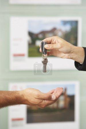 Handing over keys to new owner.