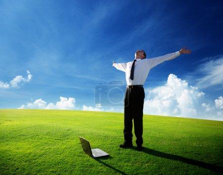 Photo pour Heureux jeune homme d'affaires sur le champ de printemps - image libre de droit