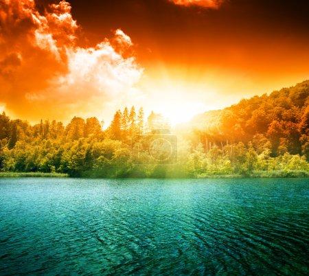 Photo pour Lac d'eau verte en forêt et coucher de soleil - image libre de droit