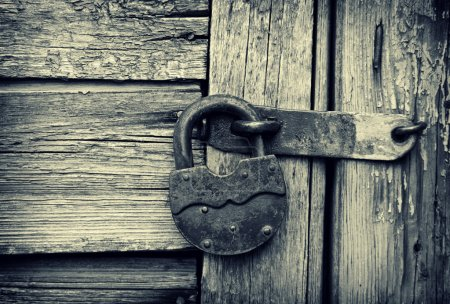 Photo for Old padlock on a wooden door, a monochrome photo. - Royalty Free Image