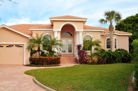 Elegant home, with huge archway covering double door entrance, flanking columns, lush tropical landscaping.