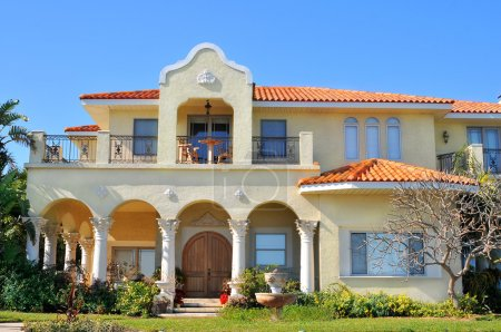 Neo-mediterranean style waterfront home with archways, recessed porches, columns, and balconies. Elegant home with a mix of spanish, italian and greek revival.